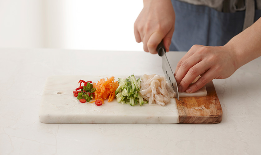 오징어는 깨끗이 손질하여 껍질을 벗긴 후 곱게 채썰고, 오이와 당근은 채썰고, 청양고추와 홍고추는 어슷썬다.