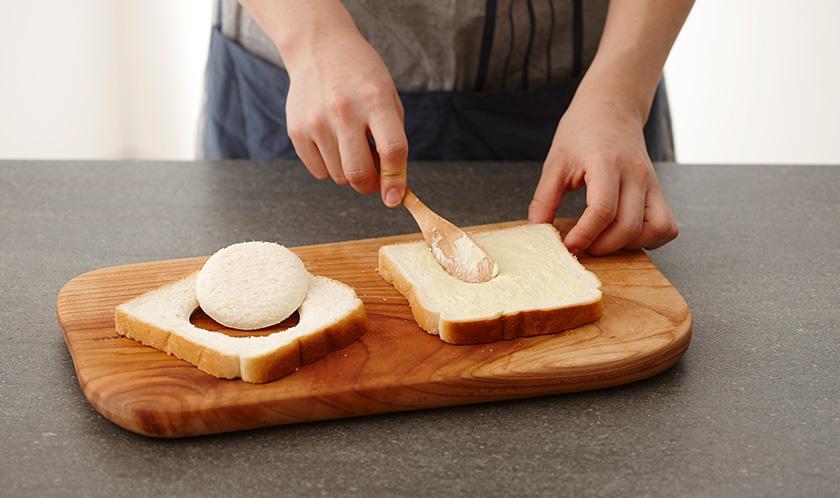 식빵 한 면에 버터를 바르고, 1장은 컵을 이용하여 가운데에 구멍을 뚫는다.