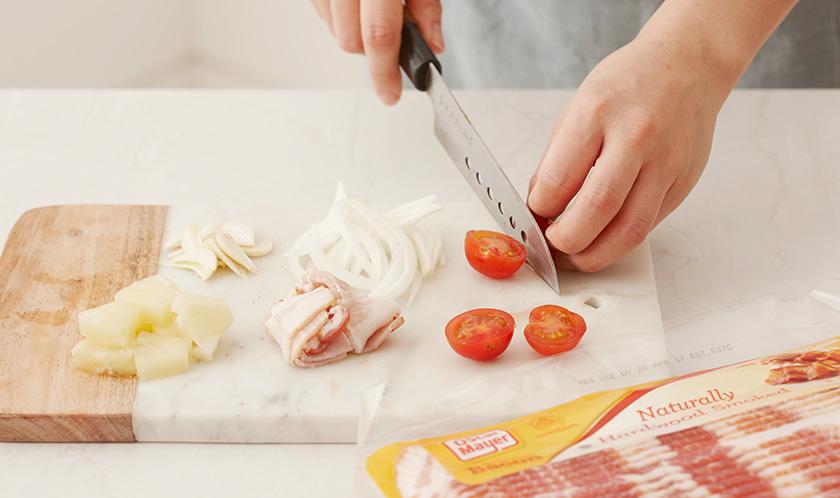양파는 0.5cm 두께로 슬라이스하고, 마늘은 얇게 편 썰고, 베이컨은 3cm 폭으로 썬다. 파인애플링은 한입크기로 썰고 방울토마토는 이등분한다.