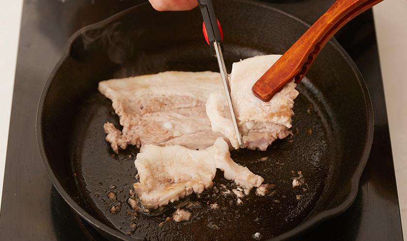 팬에 삼겹살을 구워 가위로 잘게 자른다.