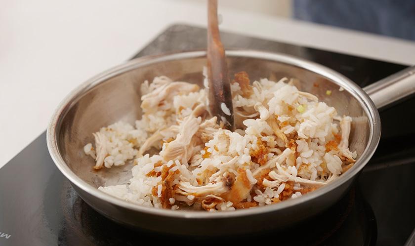 식용유를 두른 팬에 매운 치킨을 잘게 찢어 넣고, 밥을 넣어 볶는다.
