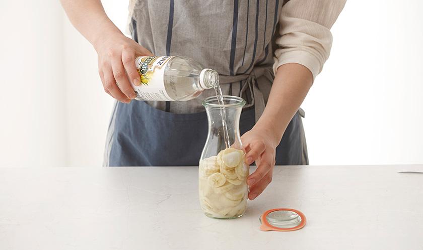저장용기에 바나나를 담고 설탕을 넣고 식초를 붓는다.