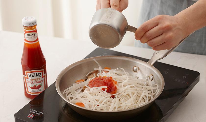 식용유를 두른 달군 팬에 양파, 당근, 골뱅이를 넣어 볶다가 불린 쌀국수와 분량의 양념 재료를 넣고 센 불에서 재빨리 볶는다.