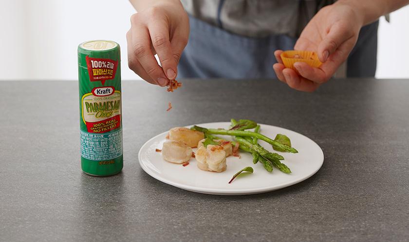 구운 베이컨을 곱게 다져 구운 가리비 위에 올리고, 아스파라거스를 곁들여낸다.