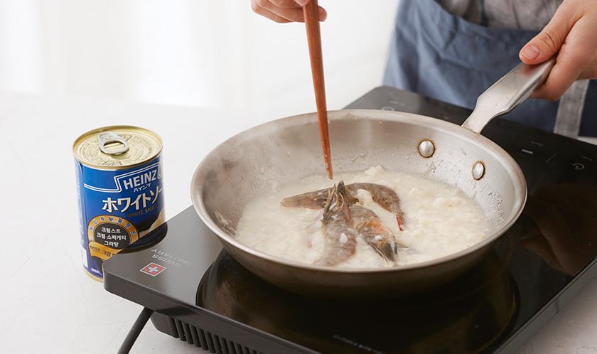올리브오일을 두른 달군 팬에 다진 마늘과 양파를 넣어 볶아 양파가 투명해지면 화이트 소스와 스파게티 삶은 물을 넣고 끓인 후 새우를 넣는다.