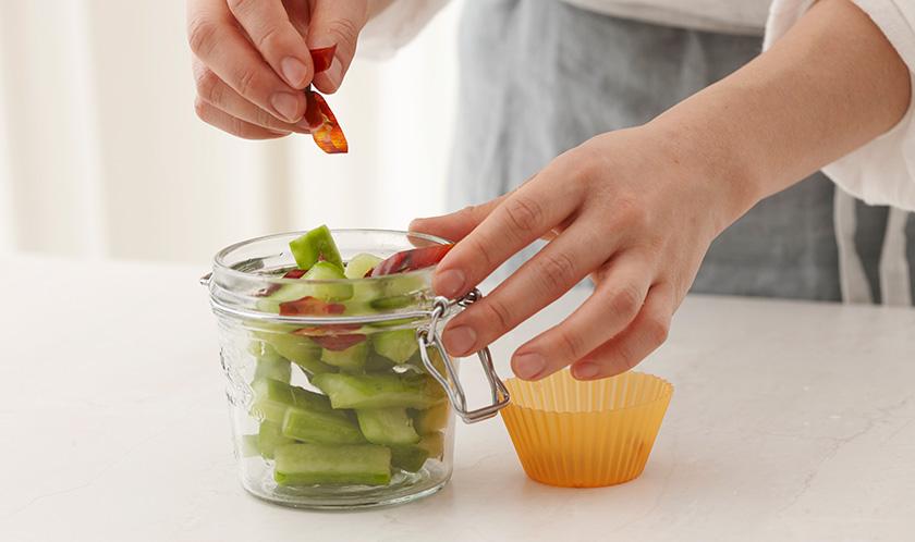 저장용기에 2, 어슷 썬 마른 고추, 통후춧가루를 넣는다.