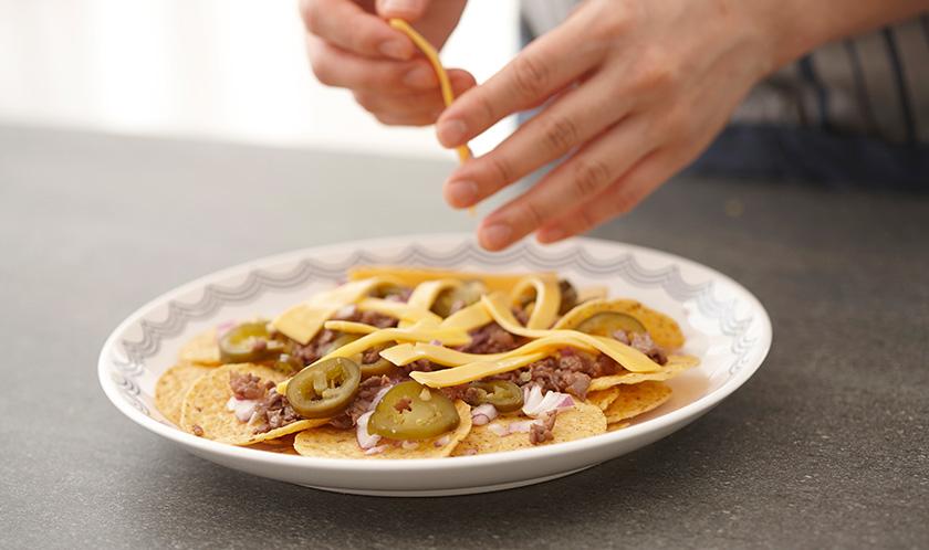 나쵸과자 위에 소고기, 적양파, 할라페뇨, 치즈를 넓게 올리고 전자레인즈로 2분간 가열한 후, 다진 이탈리안파슬리와 후춧가루를 뿌려낸다.