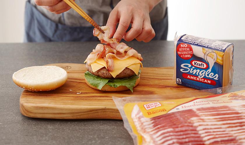 햄버거빵 사이에, 양상추, 패티, 치즈 2장, 베이컨을 넣는다.