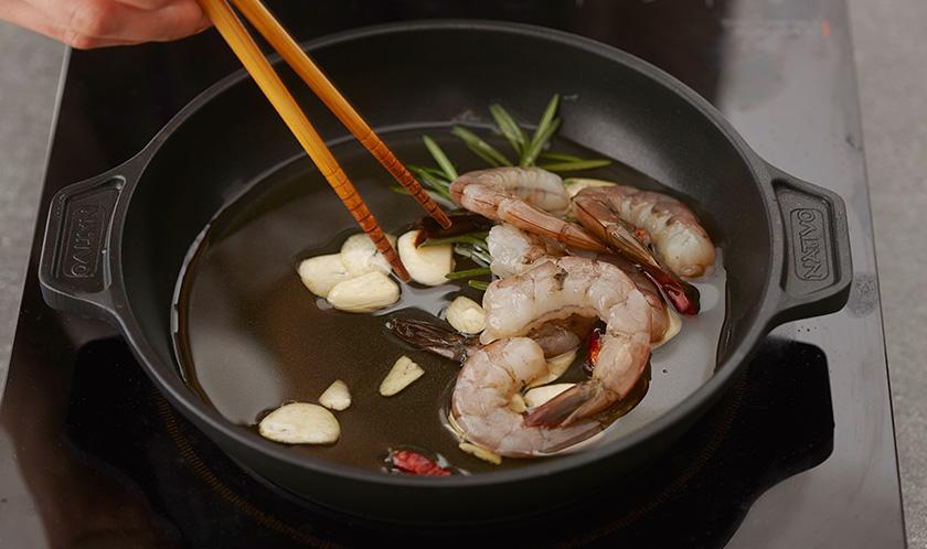 도톰한 주물팬에 새우, 마늘, 마른 고추, 로즈마리, 올리브오일을 넣어 한소끔 끓인다.