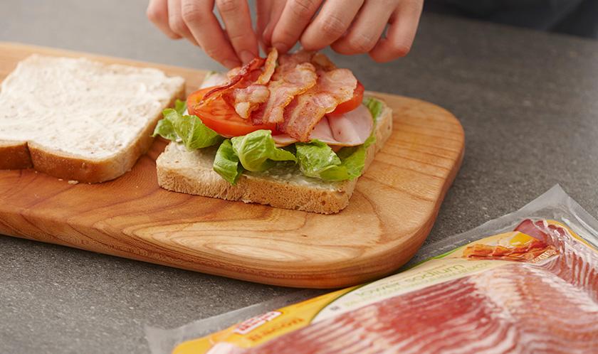 곡물식빵 사이에 상추, 슬라이스햄, 토마토, 구운 베이컨, 아이올리를 넣은 후 2등분한다.