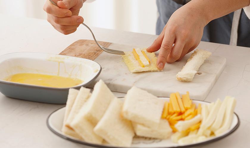 식빵에 모차렐라 치즈와 체다치즈를 길게 올리고 반으로 접은 후 가장자리에 달걀물을 묻혀 포크로 눌러 붙인다.