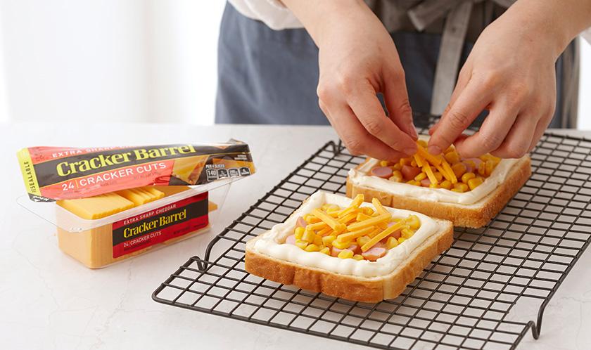 식빵 가운데에 옥수수와 링으로 썬 비엔나소시지를 올리고 그 위에 모차렐차 치즈와 체다치즈를 올린다.