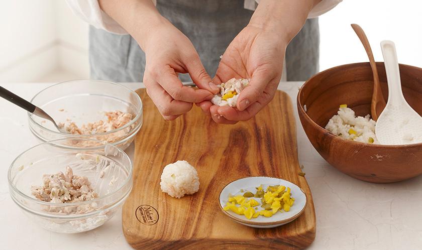 둥글게 편 밥 위에 3의 연어, 다진 치자단무지, 다진 오이지를 넣고 지름 5cm로 동그랗게 만든다.