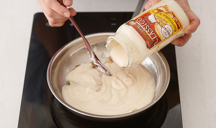 닭다리살을 꺼낸 팬에 다진 마늘과 다진 양파를 볶다, 로스티드 갈릭 알프레도를 넣어 끓인다.