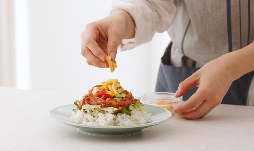 따뜻하게 데운 밥 위에 4, 양상추와 로메인, 토마토, 아보카도를 올린 후 치즈와 후춧가루를 뿌려낸다.