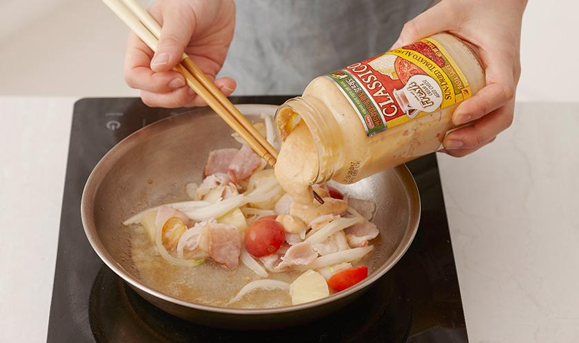 스파게티 삶은 물과 썬드라이드 토마토 알프레도를 넣어 중불에서 끓인다.