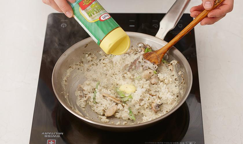 밥을 넣어 약불에서 뭉근하게 볶다, 버터와 파마산 치즈를 넣어 마무리한다.