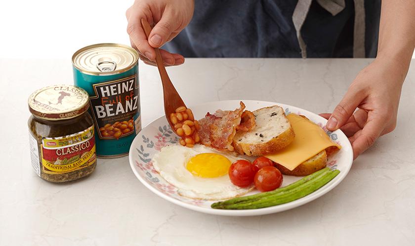 접시에 달걀프라이, 바게트, 베이컨, 베이크드빈스, 아스파라거스 방울토마토, 치즈를 담고 바질 페스토를 곁들여낸다.