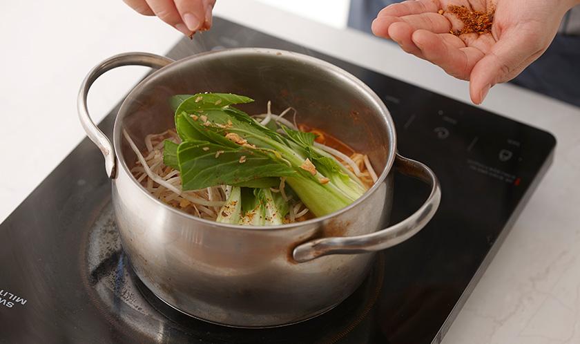 청경채와 숙주를 넣고, 땅콩가루와 카이엔 페퍼를 뿌려낸다.