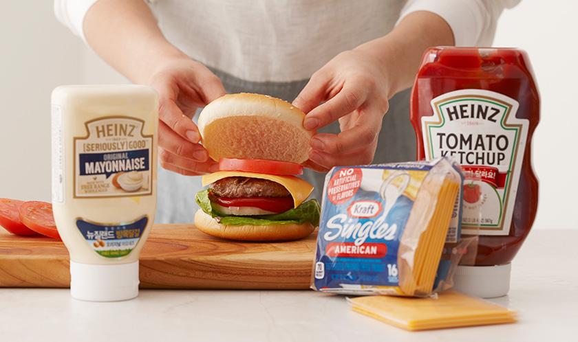 햄버거빵에 마요네즈를 바르고 상추, 양파, 케찹, 패티, 싱글즈 치즈, 토마토, 햄버거빵 순으로 올린다.