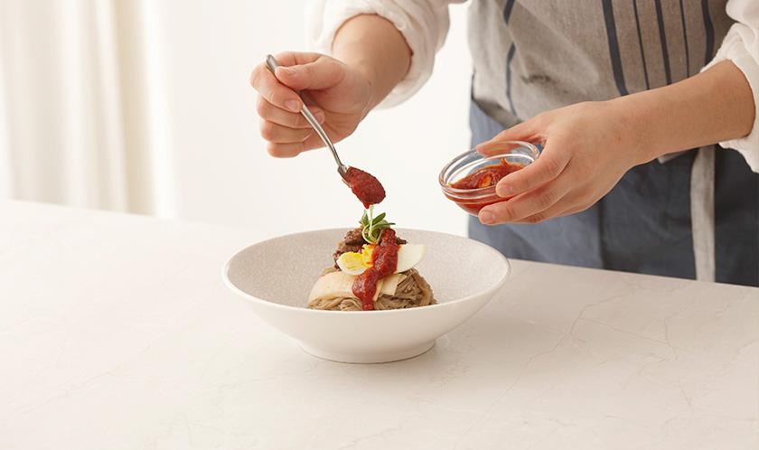 냉면은 삶아 그릇에 담고 불고기, 냉면무, 삶은 달걀, 양념장 2큰술을 얹어낸다.