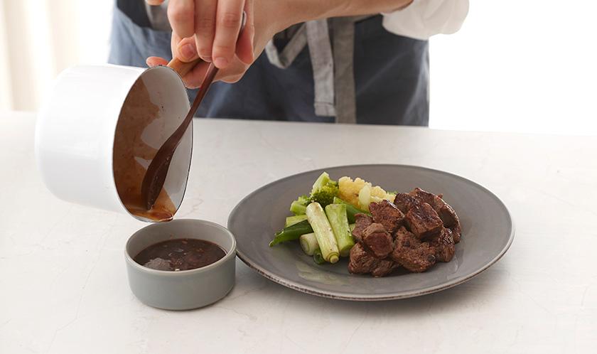접시에 소고기를 담고 대파, 브로콜리, 콜리플라워, 소스를 곁들여낸다.
