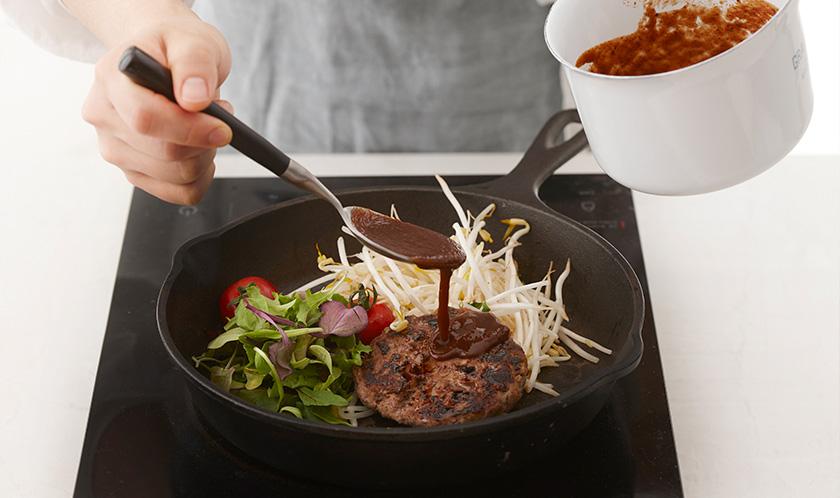 달궈진 철판팬에 함바그를 올린 후 소스를 얹고, 숙주, 어린잎채소, 수란을 곁들여낸다.