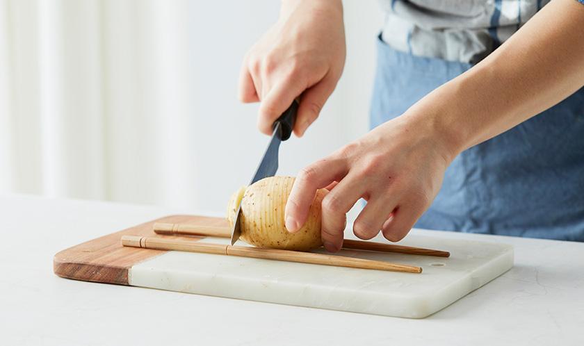 감자는 껍질째 깨끗이 씻고, 아래에 젓가락을 나란히 둔 후 칼집을 낸다.