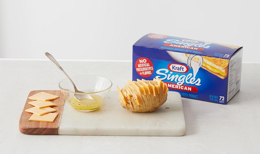 감자 칼집 사이에 싱글즈 치즈를 끼어 넣고, 녹인 버터를 솔로 바른다.