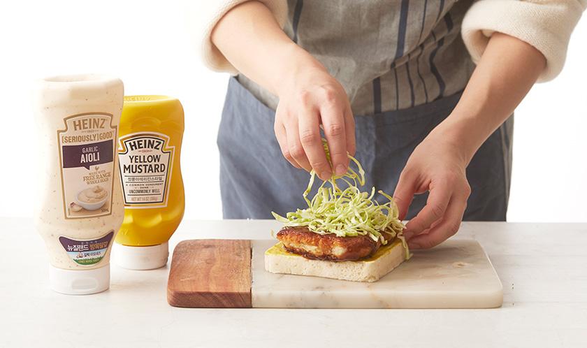 식빵 한쪽면에 아이올리와 머스터드를 얇게 바르고 돈가스와 양배추를 올린 후 식빵으로 덮는다.