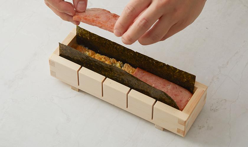 사각틀에 김을 깔고 밥-달걀-스팸-밥 순으로 넣고 김으로 감싼 후, 틀에서 꺼내 알맞은 폭으로 썬다.