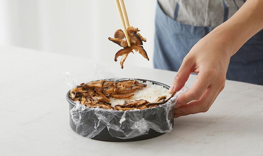 둥근 틀에 랩을 깔고 새우살-밥-오이-밥-표고버섯-밥 순으로 담는다.