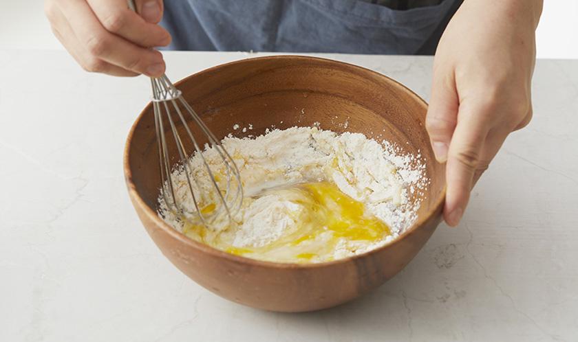 볼에 달걀, 소금, 후추, 올리브오일을 넣고 거품기로 섞다, 박력분, 우유, 피자치즈를 넣어 다시 섞는다. 다진 양파를 넣고 살짝 섞는다.