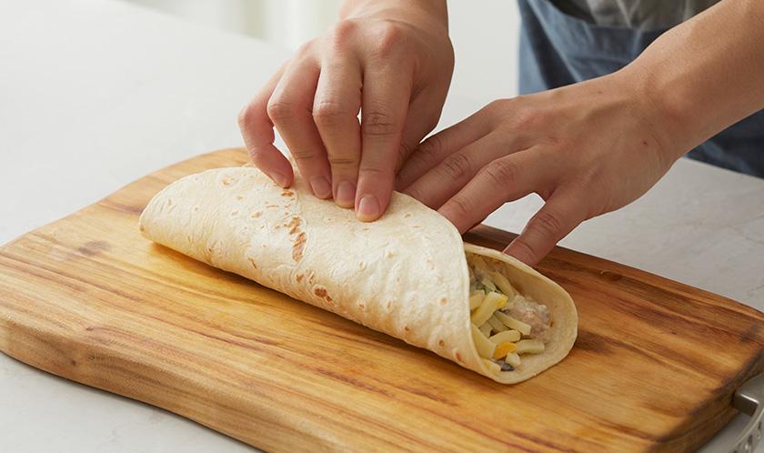 또띠아 가운데 4를 올리고 피자치즈를 올린 후 돌돌 말아 190℃로 예열한 오븐에서 10분간 굽는다.