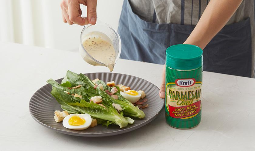 접시에 로메인을 담고 위에 베이컨, 삶은 달걀, 식빵을 올린 후, [소스]와 파마산 치즈를 뿌려낸다.