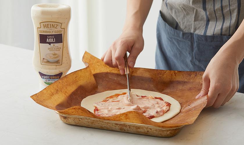 3을 동그랗게 밀어 얇게 편 후 클래시코 토마토 & 바질과 아이올리를 올려 스패츌러로 섞어가며 펴 바른다.