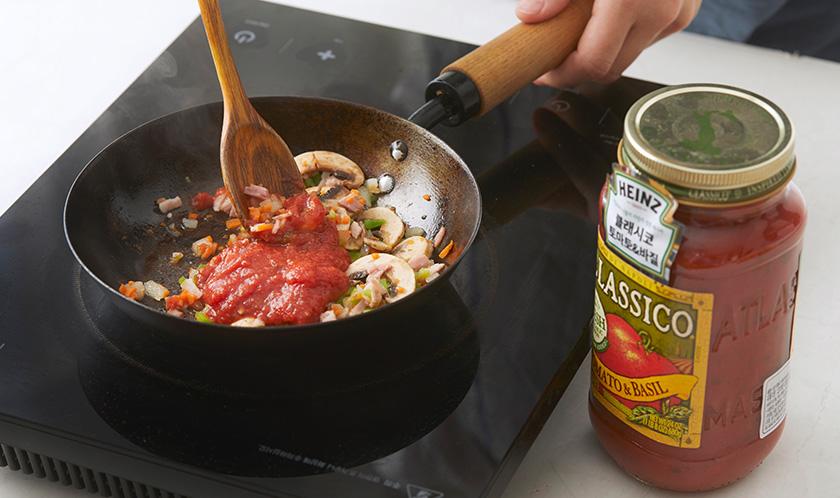 올리브오일을 두른 팬에 양파를 볶아 향을 낸 후 당근, 피망, 베이컨, 양송이버섯, 클래시코 토마토 & 바질을 넣고 물기가 없도록 볶는다.