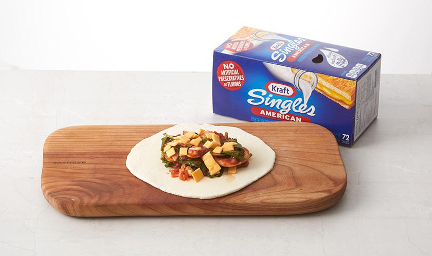 1의 반죽이 2배로 부풀면 2등분으로 나눠 밀대로 동그랗게 밀고 3과 싱글즈 치즈를 올린 후 반으로 접는다. 가장자리를 꼼꼼하게 오므려 접는다.