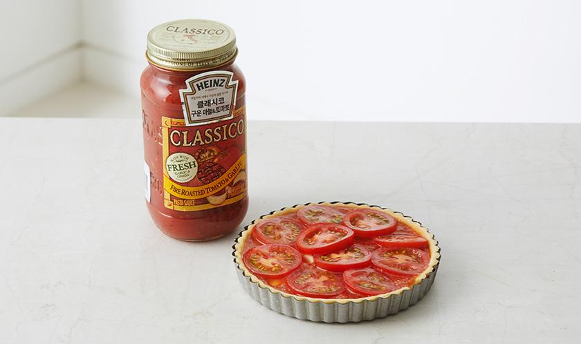 1의 반죽을 5mm 두께로 밀어 포크로 구멍을 낸 후 3을 담고 토마토를 올려 180℃로 예열한 오븐에서 30분간 굽는다.