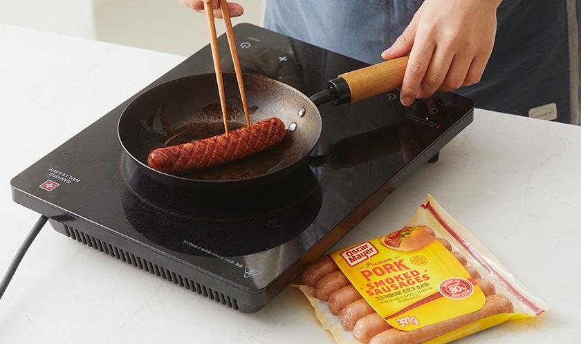 소시지에 칼집을 넣어 팬에 굽는다.