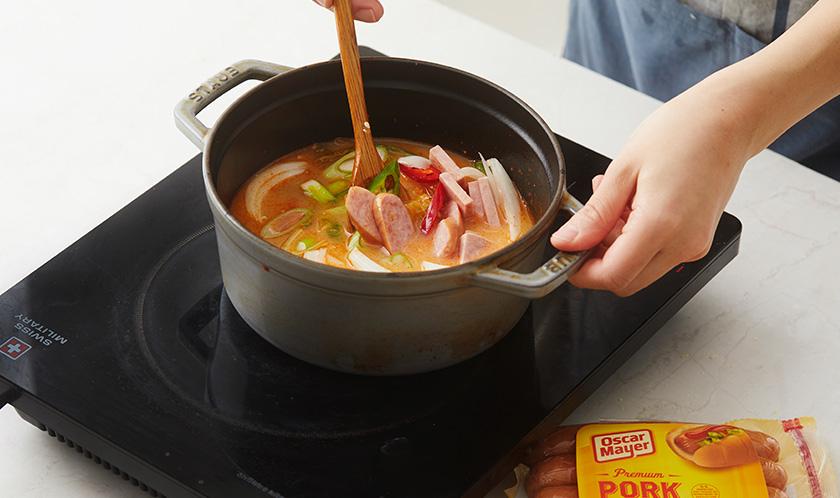 사골육수와 물을 붓고 스팸, 소시지, 양파, 대파, 풋고추, 홍고추를 넣어 한소끔 끓이다, 분량의 [양념]을 넣는다.