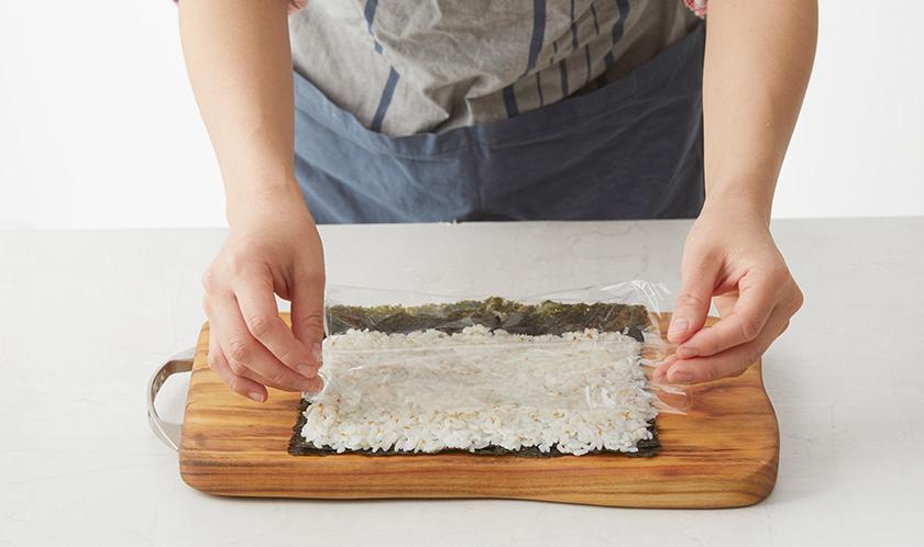 김 위에 밥을 얇게 깔고 랩을 씌운 후 뒤집는다.