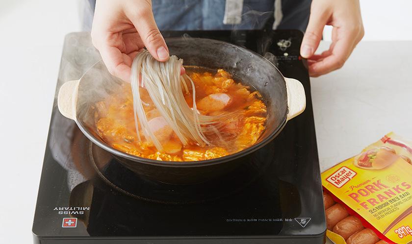 불린 당면과 대파를 넣어 끓이다, 국간장, 소금, 다진 마늘로 간을 한다.