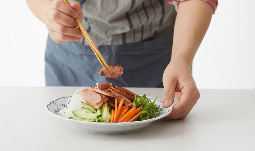 버미셀리는 삶아 찬물에 헹궈 당근, 오이, 소시지, 상추와 함께 접시에 담는다.