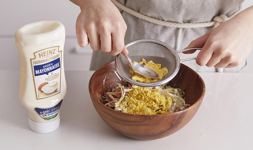 달걀노른자를 체에 내려 넣은 후 살짝 버무린다.