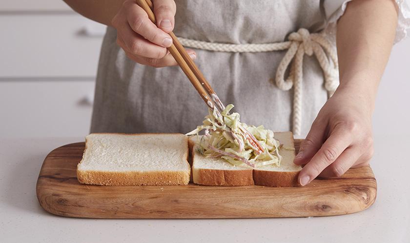 식빵 사이에 샐러드를 듬뿍 넣은 후 반 자른다.