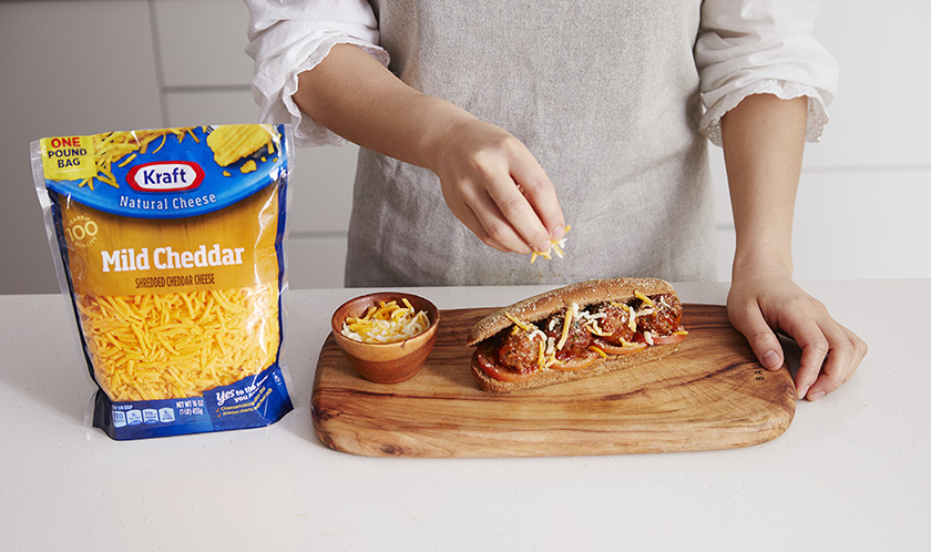 핫도그빵을 반 가른 후 토마토 슬라이스와 미트볼을 올리고, 크래프트 슈레드 마일드 체다와 크래프트 그래이트 파마산 치즈를 듬뿍 뿌려낸다.