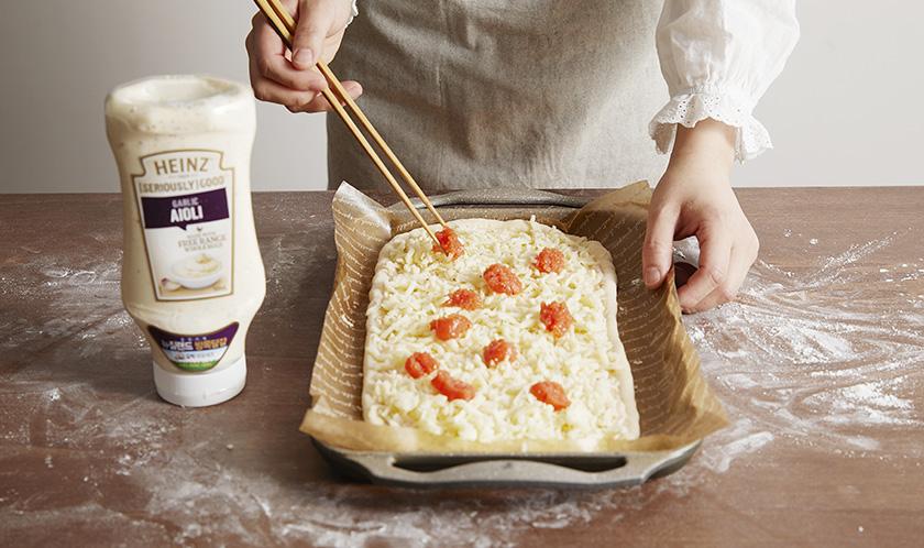 피자도우를 밀어 타원형을 만들고 2를 넓게 펴 바른 후, 크래프트 슈레드 모짜렐라와 1의 명란젓을 올린다.