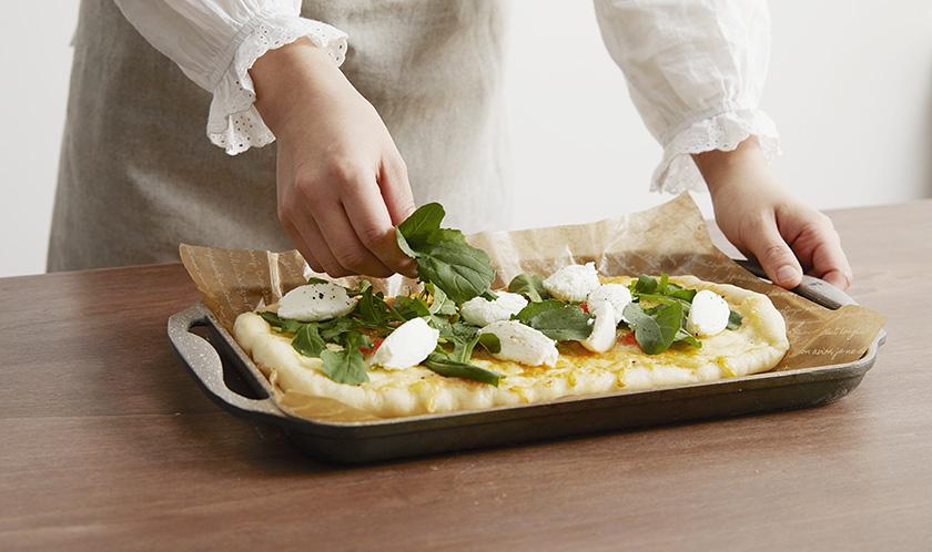 루꼴라와 리코타치즈를 고르게 올리고, 크래프트 그래이트 파마산 치즈와 후춧가루를 뿌려낸다.